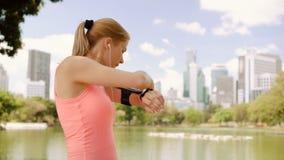 跑步在公园的妇女赛跑者 适合的女性体育健身训练 使用检查手机的smartwatch 股票录像
