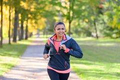 跑步在公园的微笑的妇女 免版税库存照片