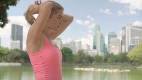 跑步在公园的美丽的少妇赛跑者 适合的女性体育健身训练 做马尾辫 股票录像