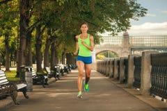 跑步在公园的运动服的妇女晴天 库存照片