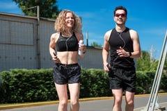 跑步在城市街道上的赛跑者夫妇  免版税库存图片
