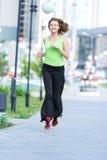 跑步在城市街道公园的妇女。 免版税图库摄影