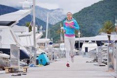 跑步在小游艇船坞的妇女 库存照片