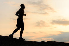 跑步在山的日落的非裔美国人的运动员人剪影  室外培训 体育和健身概念 免版税库存照片