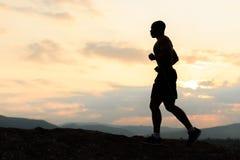 跑步在山的日落的非裔美国人的运动员剪影 室外培训 库存照片