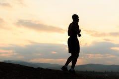 跑步在山的日落的非裔美国人的运动员剪影 库存图片