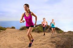 跑步在山行迹道路的远足的赛跑者户外在运动服越野耐力训练 库存照片
