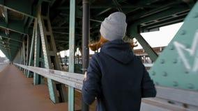 跑步在工业桥梁的慢动作幼小母赛跑者在城市 股票视频