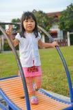 跑步在操场的逗人喜爱的亚裔女孩。 库存图片