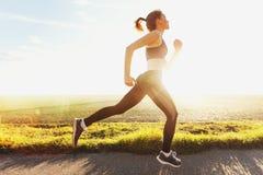 跑步在日落的美丽的女孩 免版税库存照片