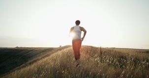 跑步在日落的连续赛跑者人 马拉松的男性慢跑者训练执行小山的赛跑在剪影 股票视频
