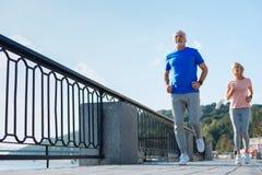 跑步在桥梁下的年长夫妇 免版税库存照片