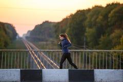 跑步在桥梁的年轻亭亭玉立的妇女早晨 库存图片