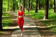 跑步在森林的连续女孩早晨 免版税库存照片