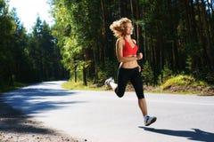 跑步在森林里的美丽的女孩 免版税库存照片