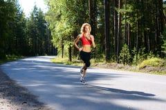 跑步在森林里的美丽的女孩 免版税库存图片