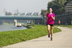 跑步在河堤防附近的女孩 免版税库存图片