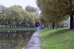 跑步在河河岸的秋天自然的年轻愉快的妇女  连续健身女孩 免版税库存图片