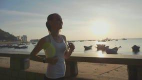 跑步在沿海岸区的年轻运动的妇女在慢动作的日出 股票录像
