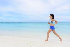 跑步在海滩的健康和活跃连续妇女 免版税图库摄影