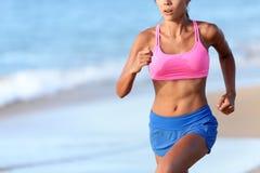 跑步在海滩的坚定的妇女的中央部位 图库摄影