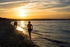 跑步在海滩的日落 库存照片