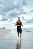 跑步在海滩的连续人在室外健身的锻炼期间 体育运动 免版税库存图片