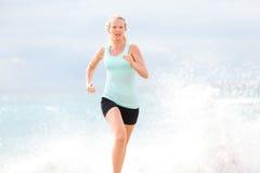 跑步在海滩的连续女子运动员 免版税库存图片