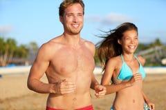 跑步在海滩的连续运动夫妇 免版税库存图片