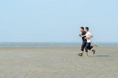 跑步在海滩的年轻人 免版税图库摄影