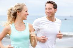 跑步在海滩谈话的锻炼连续夫妇 免版税库存照片