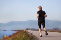 跑步在湖附近的年轻人 免版税库存图片
