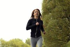 跑步在秋天公园的年轻愉快的妇女 连续健身女孩 免版税库存照片