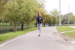 跑步在秋天公园的年轻愉快的妇女 连续健身女孩 免版税图库摄影