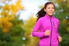 跑步在秋天的秋天森林里的连续妇女 免版税图库摄影