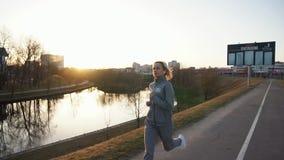 跑步在美好的日出的城市的适合的妇女 股票录像