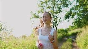 跑步在自然的年轻愉快的微笑的妇女 她听到音乐 股票视频