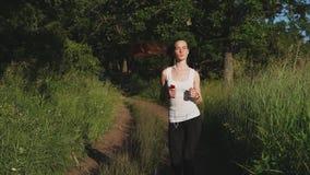 跑步在自然的年轻运动的妇女 听到音乐的她,当跑时 影视素材