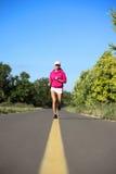 跑步在路的女孩 免版税库存照片