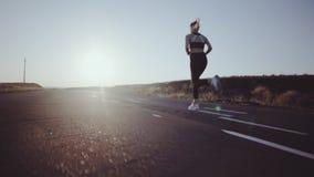 跑步在路的运动的女孩在晚上在日落 股票视频