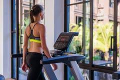 跑步在踏车的妇女水平的射击在健康体育俱乐部在豪华旅游胜地 女性解决在健身房赛跑 库存照片