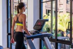 跑步在踏车的妇女水平的射击在健康体育俱乐部在豪华旅游胜地 女性解决在健身房赛跑 免版税图库摄影