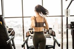 跑步在踏车的妇女水平的射击在健身俱乐部 女性解决在跑在踏车的健身房 免版税库存照片
