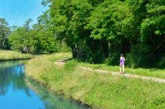 跑步在运河河附近的活跃妇女赛跑者,户外跑 免版税图库摄影
