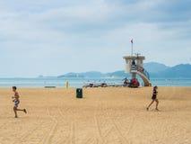 跑步在击退海湾海滩的人们 图库摄影
