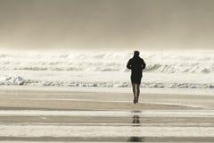 跑步在Fistral海滩,北康沃尔的年轻人 库存图片
