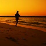 跑步在Jumeira海滩的日落期间的妇女在迪拜。 免版税库存照片