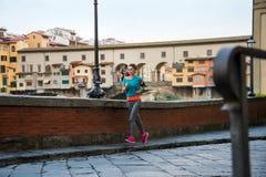 跑步在ponte vecchio附近的健身妇女 免版税库存照片