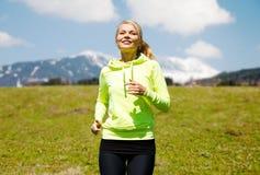 跑步愉快的年轻微笑的妇女户外 免版税库存图片