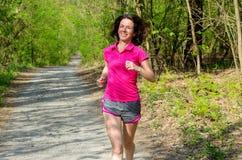 跑步户外在森林里的妇女赛跑者 库存图片